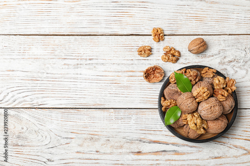 Plate with walnuts and space for text on wooden background, top view