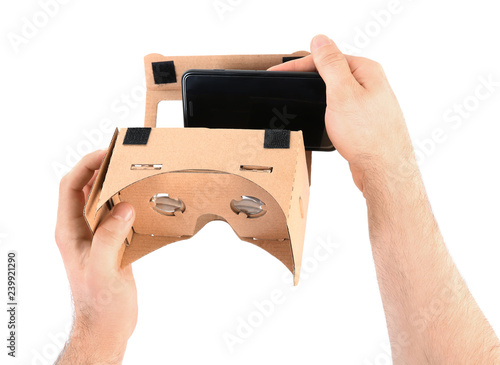Man putting smartphone into cardboard virtual reality headset on white background, closeup