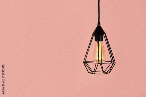 Photo  Modern hanging lamp on color background, space for text