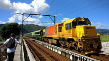 Train Passing Over Old Riverside Bridge On A Sunny New Zealand Day With The Hilly Backdrop As A Student Crosses The Bridge