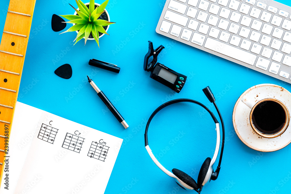 Fototapeta Desk of musician for songwriter work with headphones, keyboard, guitar and notes blue background top view - obraz na płótnie