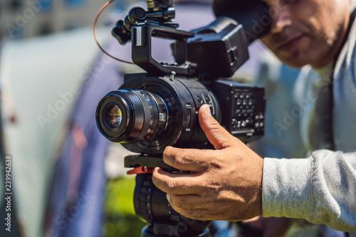 a professional cameraman prepares a camera and a tripod before shooting #239942638
