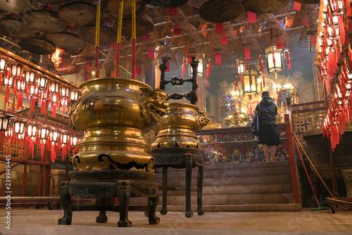 Tuinposter Aziatische Plekken Incense burners and praying woman in Man Mo Temple, Hong Kong 香港の文武廟 香炉と祈る女性
