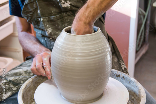 Artist potter in the workshop creating a ceramic vase. Hands closeup. Twisted potter's wheel. Small artistic craftsmen business concept.