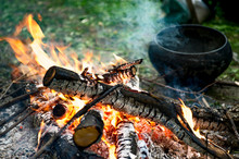 Preparing For Cooking On Fire In A Camping Trip. Pan Vintage Background. The Concept Of A Camp Kitchen