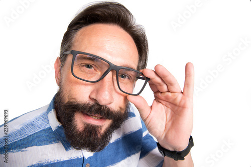 Fotografija  Close up of intelligent bearded man looking at you through glasses
