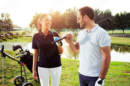 Couple at the course playing golf and looking happy - Image