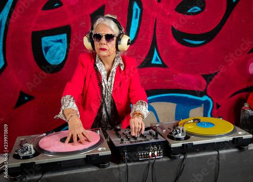 grandma dj in front of graffiti wall