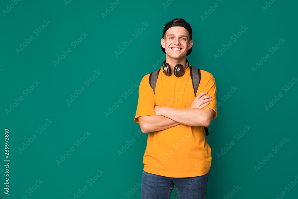 Fototapeta Happy teenager with crossed arms over turquoise background