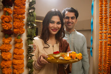 Close Up Of Happy Young Couple In Traditional Dress Standing Near The Decorated Entrance Of Their House With Pooja Plate.