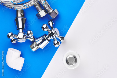 Fotografía Plumbing parts, accessories and tools on a blue white background.