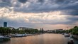 Timelapse of boats in Paris in front of Jussieu University, with a threatening cloudy and stormy sky, view from Austerlitz bridge