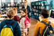 adorable schoolkid with backpack smiling at camera while visiting library with classmates