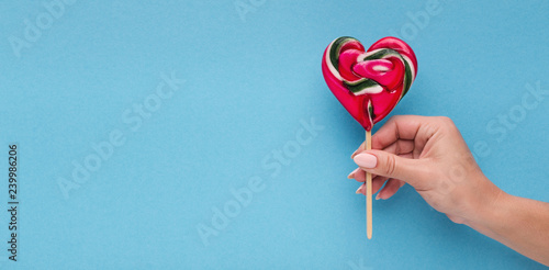 Stampa su Tela Love conceptual background, hand with heart shaped lollipop