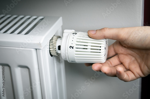 Canvas Print hand adjusting temperature on radiator. energy saving concept