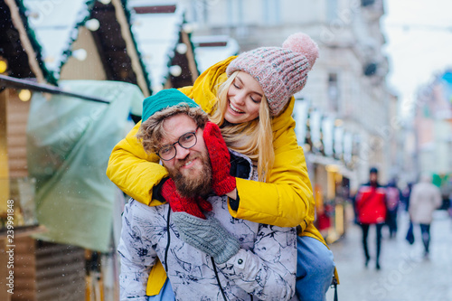 Fotografía Couple in warm bright outwear, man giving piggyback to woman in street, outdoor