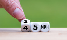 "Hand Is Turning A Dice And Changes The Expression ""45 MPH"" To ""35 MPH"" As Symbol To Reduce The Speed Limit From 45 To 35 Miles Per Hour"