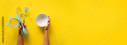 Woman hand holding kitchen utensils on yellow background. Baking tools - bowl, brush, whisk, spatula. Bakery, cooking, healthy homemade food concept. Copy space