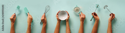Fotografering Female hands holding kitchen tools, sieve, rolling pin, bowl, sieve, brush, whisk, spatula for baking and cooking over pastel blue background