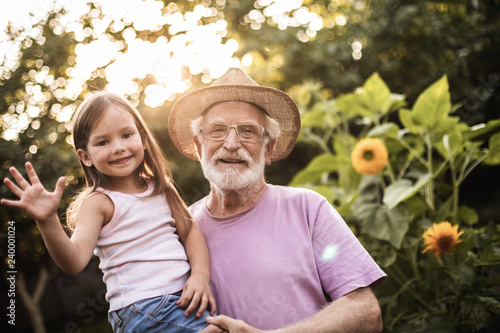 Foto  Elderly man with his granddaughter standing between flowers