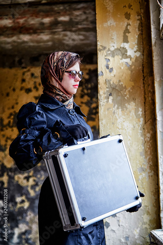 Fotografía  Girl in a black cloak, a scarf and a diplomat in an abandoned house near window
