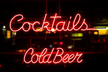 Vintage Ocktails And Cold Beer Neon Sign Hanging In A Bar Window