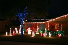 House Adorned With Christmas Holiday Lights And Decorations Including Santa Snowman And Giant Trees Illuminated At Night
