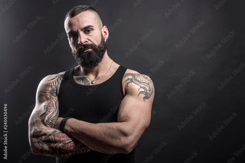 Fototapeta Uomo muscoloso e tatuato con braccia conserte guarda deciso in macchina - sfondo nero