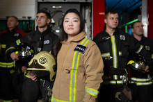 Portrait Of Four Male And Female Firefighters On Background Of Fire Truck