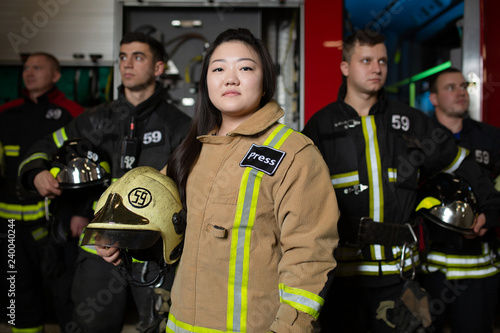 Photographie Portrait of four male and female firefighters on background of fire truck