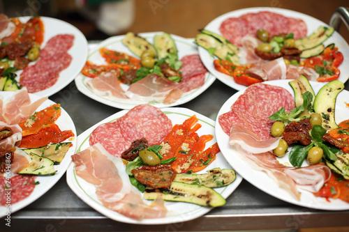 Talerze z jedzeniem, wędlina, warzywa, owoce w restauracji.