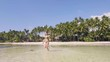 Happy woman in swimsuit running on sea at paradise beach on palm tree landscape