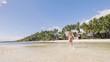 Carefree woman running on sea water on summer beach. Girl on paradise beach