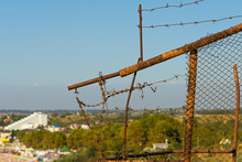 Old Rusted Fence With Barbed Wire On The Background Of An Abandoned Building In The Background