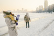 Young Caucasian people in love heterosexual couple have a date in winter near a frozen lake. Active holiday holiday Valentine's Day, playing snowballs and playing joy