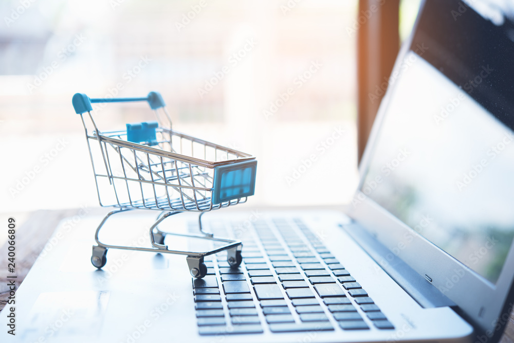 Fototapety, obrazy: Online shopping concept. Shopping cart with laptop on the desk.