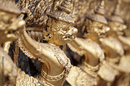 group of golden Garuda statue stand around , the bronze symbol of Thai government, giant ancient gold eagle with crown sculpture antique signature on temple royal palace wall