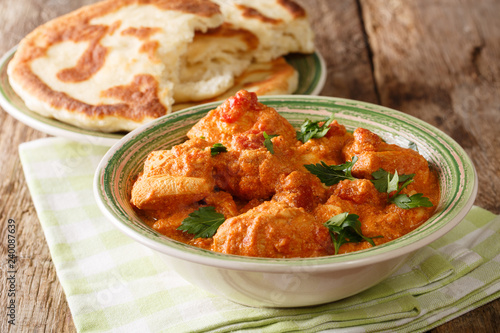 Indian traditional Karhai chicken recipe in thick tomato sauce close up and naan on the table. horizontal