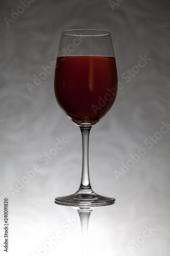 Glass goblet with wine stands against blurred background