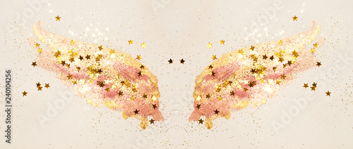 Foto  Golden glitter and glittering stars on abstract pink watercolor wings in vintage nostalgic colors
