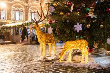 Decorated and illuminated spotted bambi deers under the christmas pine-tree on the Red square fair