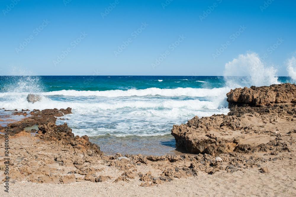 Fototapeta Scenic rocky beach with wave splatters