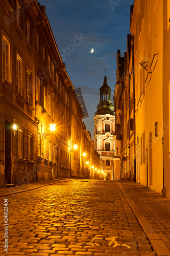 Fotografiet A cobbled street with a baroque belfry of a historic monastery at night in Poznań
