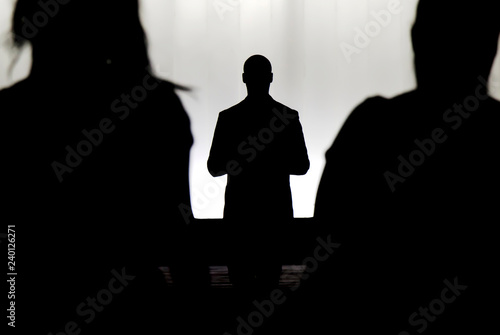 Fotografering  Silhouettes of a mystery man standing , watching and confronting two blurry pers