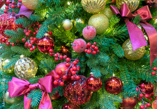 Christmas tree decorated with colorful toys bows and berries. Christmas background.