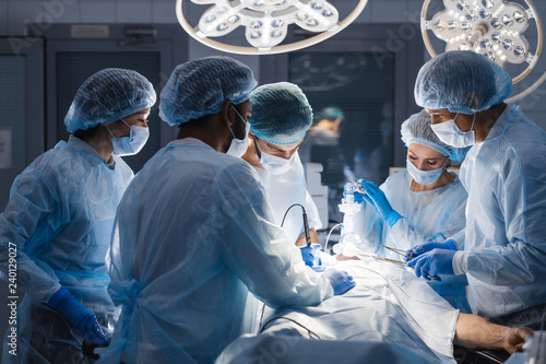 Tela Group of concentrated surgeons engaging in rescue of male patient in operation r