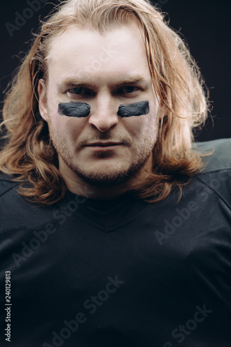 Portrait of determined caucasian blonde American football sportsman in black uniform with painted black stripes under his eyes on his face posing against black background