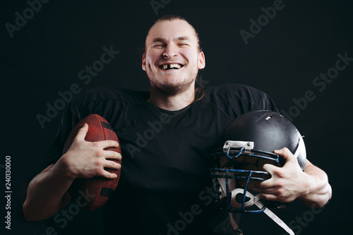 Satisfied cheerful handsome american caucasian man grins at camera, having his tooth knock out during a football match, but happy to win, isolated over black concrete background.