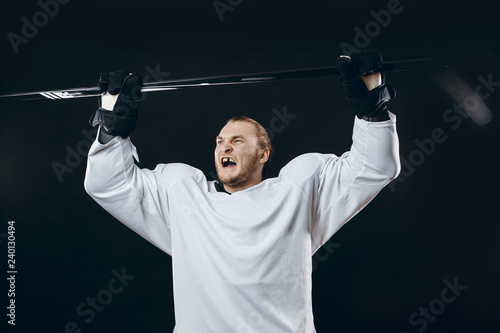Portrait of cheerful handsome hockey player getting into the mood for winning before game starts. Sportsman in white uniform celebrating the victory. Sport, Achievements and People concept
