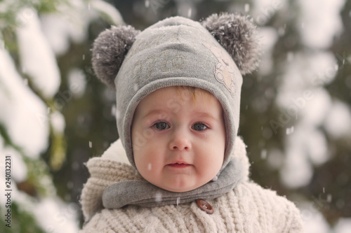 291d7fe7c9e Cute little boy in winter. Kinder in winter clothes walking under the snow.  Pretty
